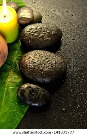 wet massage stones with green leaf and water drops - stock photo