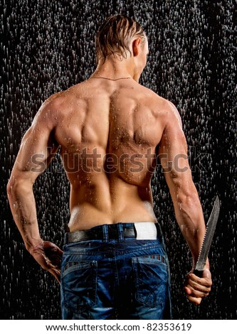 Wet muscle sexy young man back under the rain with knife in studio - stock photo
