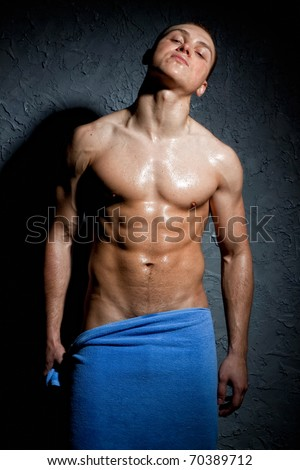 Wet Muscular Man Wrapped in a Towel - stock photo