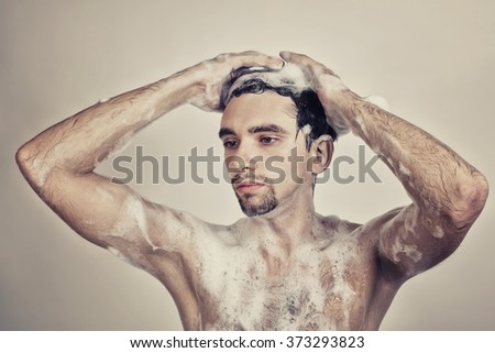 Wet naked young man in foam - stock photo