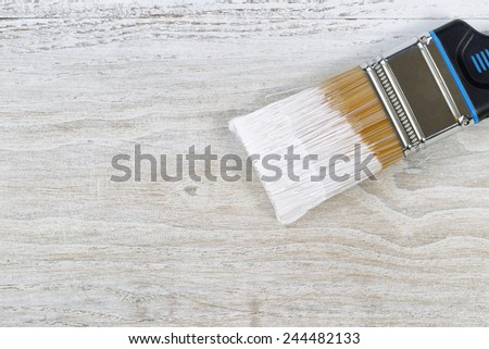 Wet paint brush on old white wooden boards - stock photo