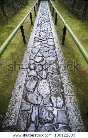 Wet paved footpath between bamboo railings in the formal garden at Koto-in, a sub temple of Daitoku-ji in Nara , Japan - stock photo