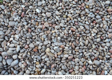 wet pebble stones on sea beach, abstract  background - stock photo
