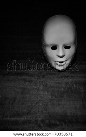 Wet plastic mask on a dark wooden background - stock photo