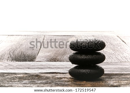 Wet polished smooth hot massage black stones with water drops droplets in Zen style cairn on vintage wood board table in relaxing wellness holistic spa for relaxation and health rejuvenation treatment - stock photo