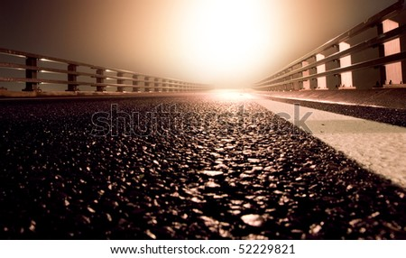 Wet road leading to bright light - stock photo