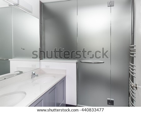 Wet room frosted glass walls and door installed in remodeled bathroom - stock photo