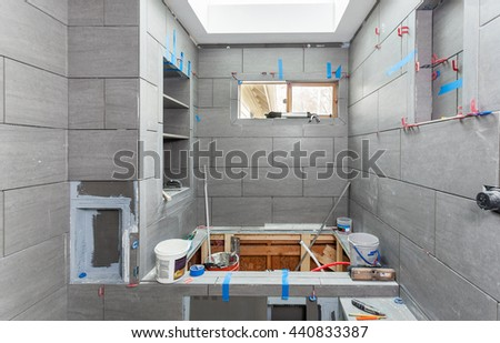 Wet room tiling in progress, including shelves, soap niche, toilet paper niche and shower seat - stock photo
