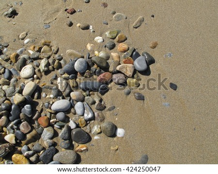 Wet sand background with sea pebbles - stock photo