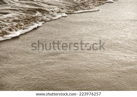 Wet sandy beach coastline closeup retro style - stock photo