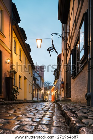 Wet street of historical Stralsund in Northern Germany. Focus on wet shiny cobblestones. - stock photo