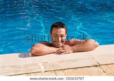 wet tanned young man posing in the swimming pool - stock photo