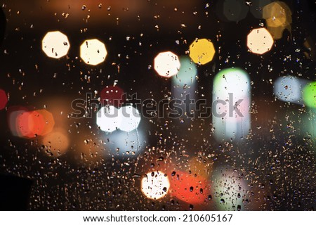 Wet the window with the background of the night city. - stock photo