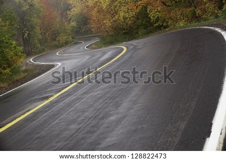 Wet winding road in autumn with rising mist. - stock photo