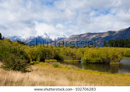 Wetland swamp in glacial Rees Dart river valley near Glenorchy with Mt Aspiring National Park, Southern Alps, vista backdrop forming an iconic New Zealand landscape - stock photo