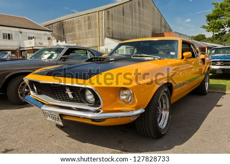 WEYBRIDGE, SURREY, UK - AUGUST 19: An immaculate orange 1969 Ford Mustang Shelby on show at the annual Brooklands Motor Museum Mustang Meet in August 19 2012. - stock photo