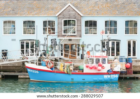 WEYMOUTH, UK - JUNE 15: Restaurant building and fishing boat on the picturesque quayside of Weymouth Harbour, UK - June 15, 2013 - stock photo