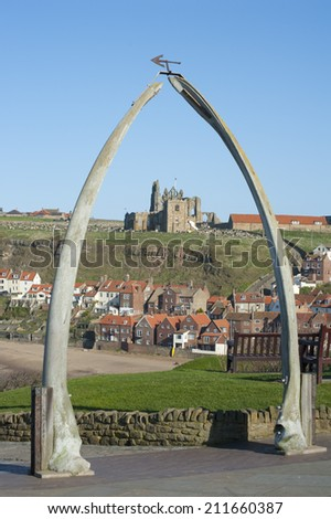Whalebone arch in Whitby, North Yorkshire, constructed from two jaw bones to commemorate whaling in the region framing the ruins of Whitby Abbey on Tate Hill - stock photo