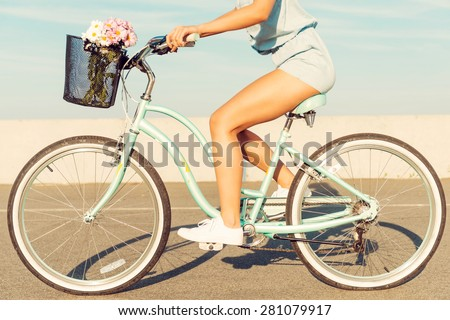 What a beautiful scenery! Smiling young couple riding on bicycle while man pointing away  - stock photo