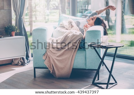 What a great morning! Beautiful young woman stretching out hands and smiling while lying in a big comfortable chair at home  - stock photo