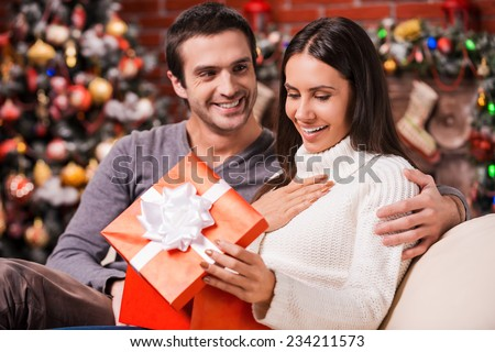 What a great surprise! Beautiful young woman opening a gift box and smiling while her boyfriend sitting close to her on the couch with Christmas decoration in the background - stock photo