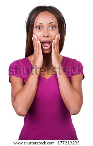 What a surprise! Surprised young African woman holding her head in hands while standing isolated on white  - stock photo