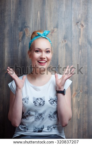 What a surprise! Young attractive amazed woman gesturing against wooden wall. - stock photo
