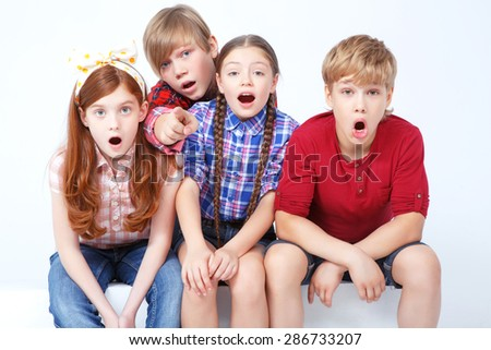 What a surprise. Young friends sitting together and expressing wonder. - stock photo