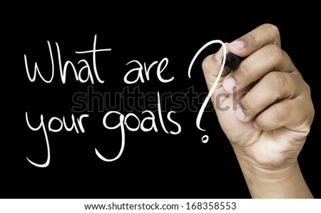 What are your goals hand writing with white marker on transparent wipe board - stock photo