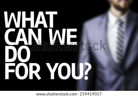 What Can We Do For You? written on a board with a business man on background - stock photo