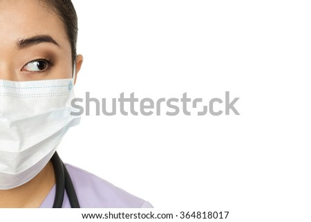 What do we have here? Cropped studio half face closeup of a female doctor wearing surgical mask looking at the copy space on the side - stock photo