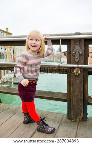 What do you mean, I can't hold on tight? See? I can do it! A little girl looks back over her shoulder, teasing and happy. - stock photo