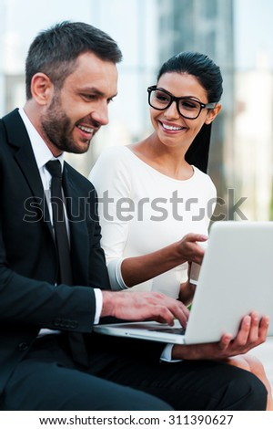 What do you think? Two smiling young business people working on laptop and discuss something while sitting outdoors - stock photo