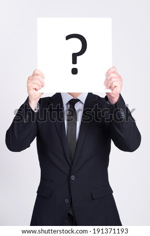 What is an answer? Businessman holding a question mark sign in front of his face - stock photo