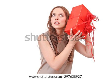 What is inside. Surprised attractive red-haired lady holding big red present near her ear against isolated white background - stock photo