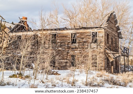 What is left of an old hotel in a Montana ghost town is being hidden by aspen trees. - stock photo