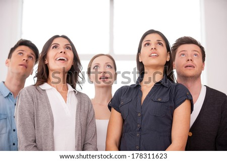 What is that? Surprised group of young people looking up while standing close to each other - stock photo
