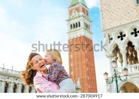What makes Venice even more magical are kisses... Here, a little girl gives her mother a kiss on the cheek while her mother holds. The mother is laughing and delighted. - stock photo