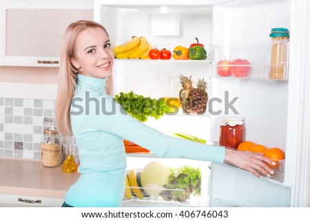 What's for dinner? Pretty blonde standing near open fridge full of food. Back view photo of thoughtful young woman. She looking at camera - stock photo