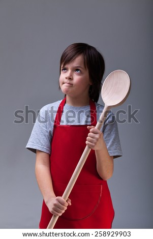 What should I cook today - young chef boy with large wooden spoon - stock photo