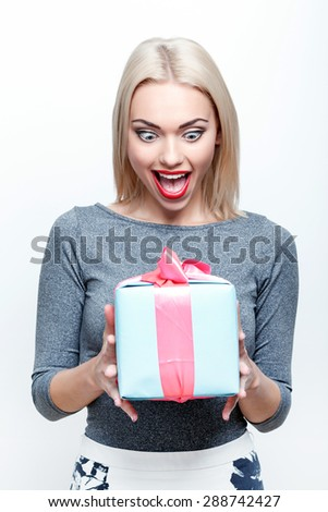 What surprised. Young blond-haired woman getting big present with great amazement on white isolated background - stock photo