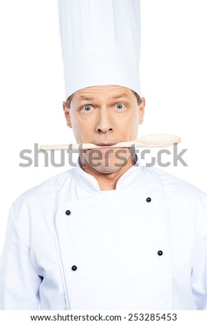 What to cook? Surprised mature chef in white uniform holding wooden spoon in his mouth while standing against white background - stock photo