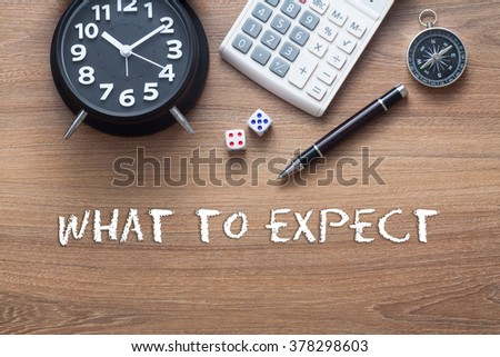 What to expect written on wooden table with clock,dice,calculator pen and compass - stock photo