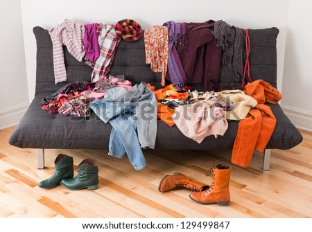 What to wear? Messy colorful clothing on a sofa. - stock photo