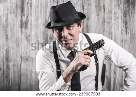 What will you say now? Bossy senior man in gangster clothing holding a gun and smiling while sitting at the chair against grey wall - stock photo