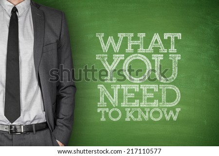 What you need to know on blackboard with businessman - stock photo