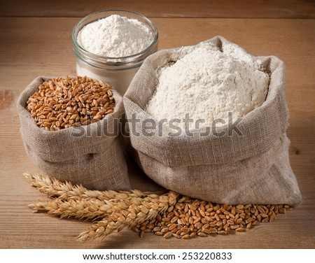 Wheat and flour in the bag, jar on the boards. Spikelets - stock photo