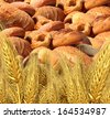 Wheat bread harvest food and agriculture farming concept with a group of baked goods from a bakery or home cooking and a field of durum semolina plants growing on a farm. - stock photo