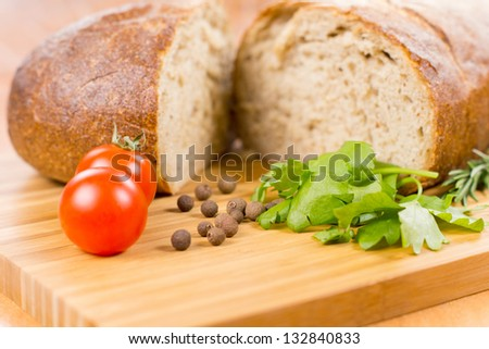 Wheat bread with herbs and tomatoes on a wooden board - stock photo