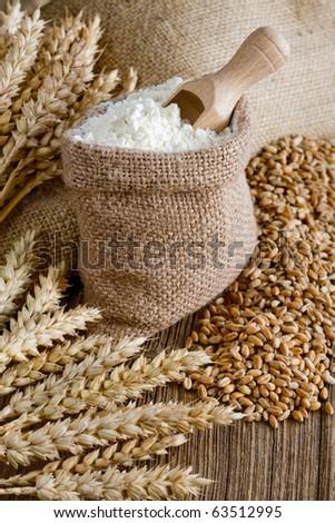 Wheat ears and flour in burlap bag - stock photo